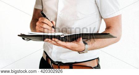 A businessman writing on his agenda
