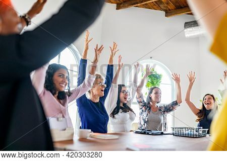 Happy women raising their arms in a meeting