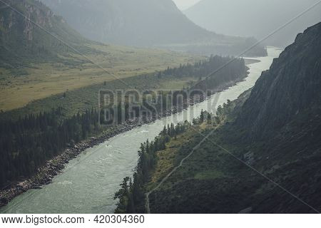Misty Mountain Landscape With Wide Mountain River. Dark Green Gloomy Scenery With Confluence Of Two