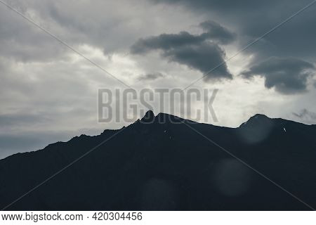 Dark Atmospheric Landscape With Black Silhouettes Of Mountains Under Gray Cloudy Sky In Rainy Weathe