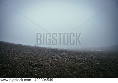 Black Stone Field In Dense Fog In Highlands. Empty Stone Desert With Sharp Stones In Thick Fog. Zero
