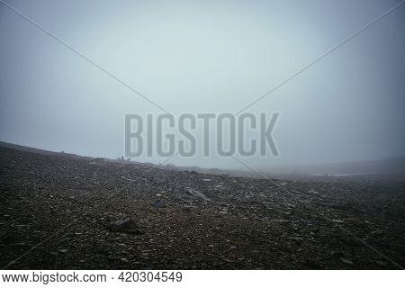 Black Stone Field In Dense Fog In Highlands. Empty Stone Desert With Sharp Stones In Thick Fog. Zero