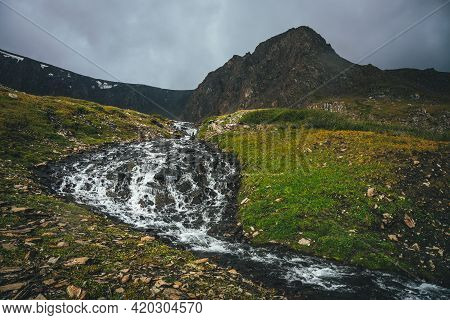 Atmospheric Alpine Landscape With Beautiful Mountain Creek In Green Valley And Great Brown Sharp Pin