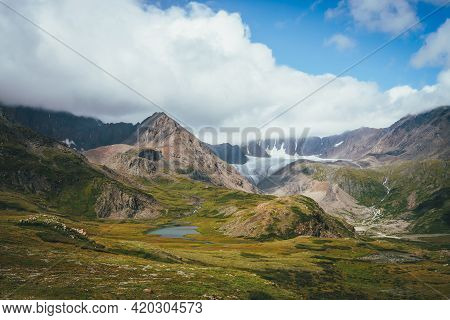 Scenic Alpine Landscape With Mountain Lake In Sunlit Green Valley And Glacier Under Cloudy Sky. Awes