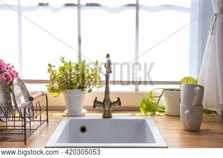 Countertops With Plants, Dish Racks, And Windows With White Shutters In The Kitchen Interior. Kitche
