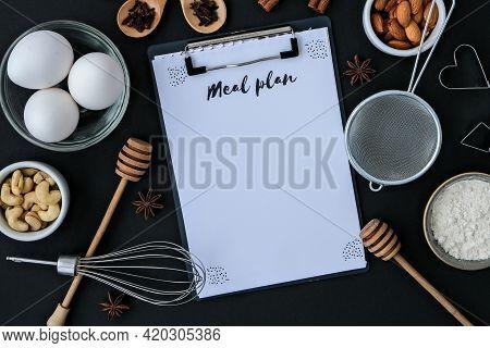 Menu Plan Baking Cooking Ingredients On Black Background. Top View. Blank Clipboard Copy Space. Home