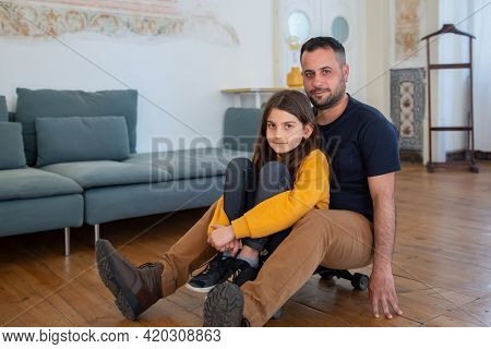 Cheerful Daughter And Father Sitting On Longboard At Home. Caucasian Girl Curling Her Legs And Beard