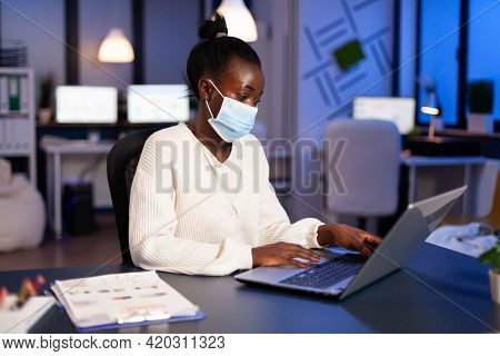 African Woman With Face Mask Reading Emails Late At Night To Respect Deadline Of Project Working In