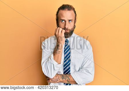 Handsome man with beard and long hair wearing business clothes looking stressed and nervous with hands on mouth biting nails. anxiety problem.