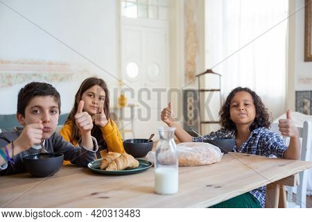 Cheerful Kids Sitting At Table In Kitchen And Showing Thumbs Up. Caucasian Girl And Boys Enjoying Th
