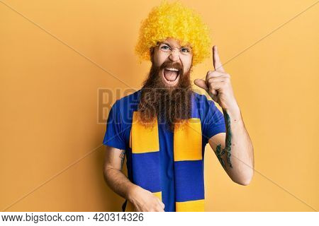 Redhead man with long beard football hooligan cheering game wearing funny wig pointing finger up with successful idea. exited and happy. number one.