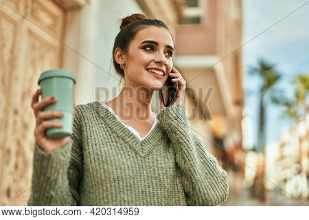 Beautiful brunette woman smiling happy and confident outdoors at the city on a sunny day of autumn speaking on the phone