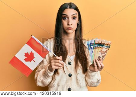 Beautiful brunette young woman holding canada flag and dollars puffing cheeks with funny face. mouth inflated with air, catching air.