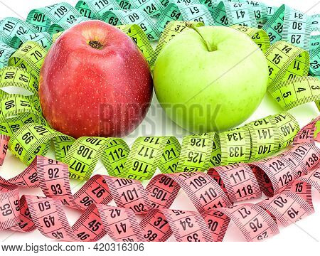 Bright Colored Measuring Tapes, Twisted In A Spiral Around A Red And Green Apple, Isolated On A Whit