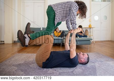 Happy Dad Lying On Floor And Lifting His Son. Curly-haired Boy Balancing On Daddys Hands And Happy T