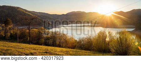 Sunset in mountain landscape. Mountain lake in sunset. Sunset on mountain lake landscape. Meadow and mountains landscape. Blue mountains and last sun lights landscape. Sunset in mountain forest. Landscape. Mountains. Sunset.