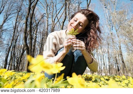 Woman Enjoying Smell Of Spring Flowers. Smiling Woman Among Spring Flowers.