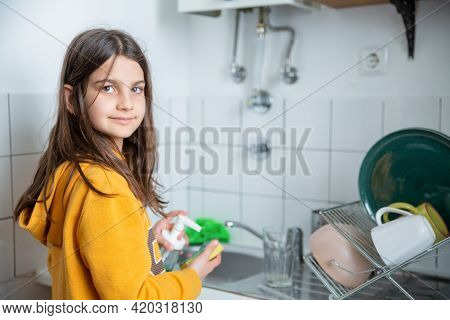 Cheerful Girl Standing And Holding Sponge And Detergent. Caucasian Kid Helping Parents, Washing Dish