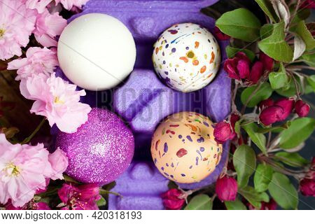 Four Eggs Decorated With Wax And Glitter In A Purple Egg Wrapper And Branches Of Ornamental Cherries
