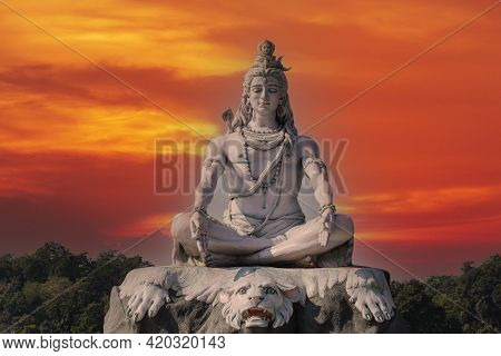 Statue Of Meditating Hindu God Shiva Against The Red Sky On The Ganges River At Rishikesh Village In