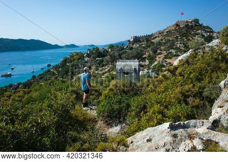 Male tourist standing on hill at Kalekoy with view of Lycian rock tombs and Simena fortress with Turkish flag, Mediterranean sea coast, Turkey