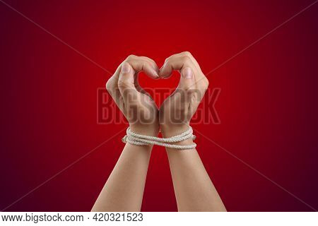 Hands In The Shape Of A Heart Tied With Rope. Concept Of The Love Of Bdsm Or Codependency