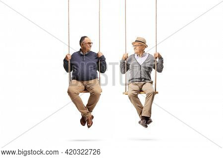 Two elderly men swinging on wooden swings and looking at each other isolated on white background