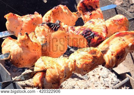 Meat Frying On Grill. Fried Pieces Of Pork And Beef Skewers On Coals In Open Air. Barbecue Meat Back