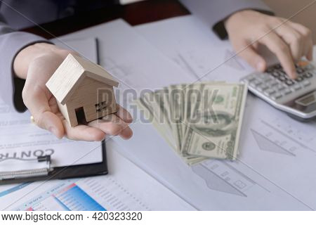 Real Estate Agent Showing A Miniature Model House To The Customer And Using Calculator. Concept For