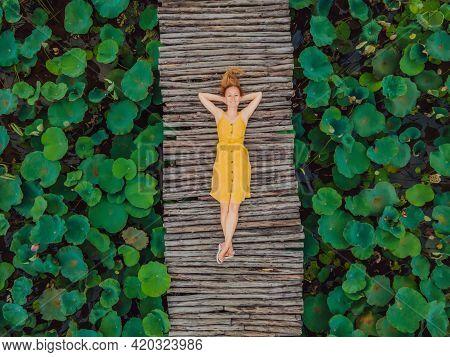 Young Woman In A Yellow Dress On The Path Among The Lotus Lake. Mua Cave, Ninh Binh, Vietnam. Vietna