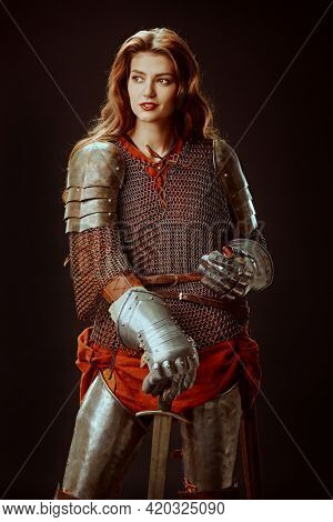 Era of romanticism. Portrait of a beautiful female knight in armor of noble birth holding a sword. The Middle Ages history.