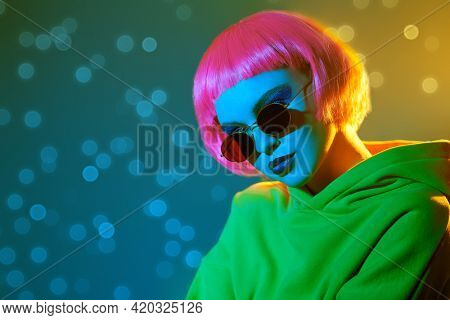 Modern girl with bright makeup and pink hair poses in red sunglasses and yellow suit in mixed color light. Sport chic fashion. Youth fashion and beauty trends.