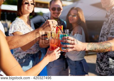 Group Of Friends Having Fun At Poolside Summer Party, Clinking Glasses With Colorful Summer Cocktail