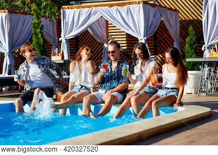Group Of Friends Having Fun At Poolside Party Clinking Glasses With Fresh Cocktails Splashing Water