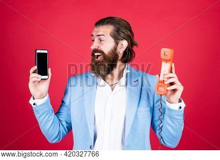 Well Groomed Man In Wedding Formalwear Has Beard Use Retro Phone And Modern Smartphone, Technology
