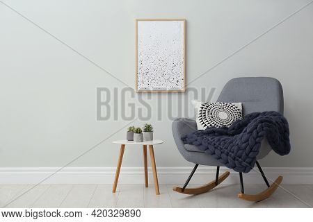 Knitted Merino Wool Plaid And Pillow On Rocking Chair In Room. Space For Text