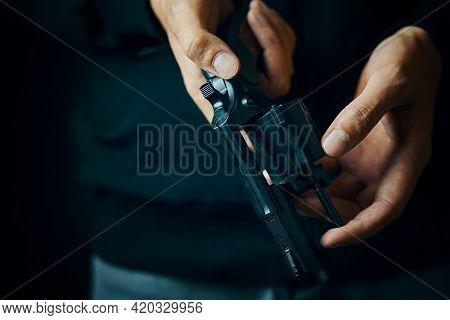 Mens Hands Check For Bullets In Revolver Barrel. Close Up Of Person Reloading Gun. Guy Prepares Pist