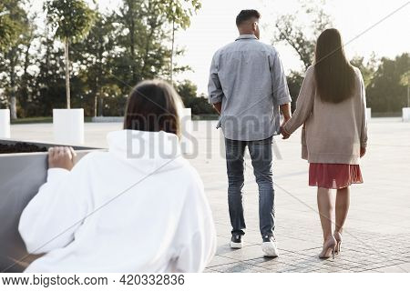 Young Woman Spying On Her Boyfriend Outdoors, Back View. Cheating Concept
