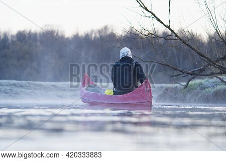 Young Man Rowing Canoe In Early Spring Morning. Lifestyle. Morning Landscape, Fog By The Morning Riv
