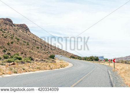 National Road N1 At Three Sisters In The Northern Cape Karoo. A Vehicle And Road Signs Are Visible