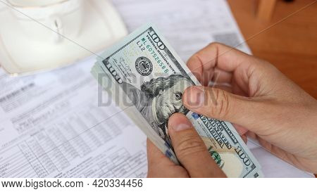 Family Budgeting. Man Counting American Dollar Bills Close-up