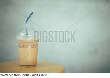 Cool Of Mocha Coffee In Take Away Glass With Brown Paper Sleeve On Wood Chair