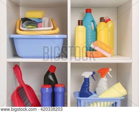 Shelving Unit With Different Cleaning Supplies And Tools On Shelves