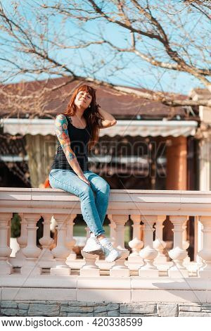 A Young Woman Sits On The Balustrade Smiling Sweetly. Vertical Orientation. Outdoor.