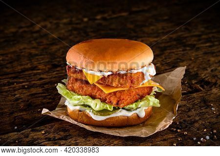 Close-up Of A Tasty Double Hamburger With Cheese And Deep Fried Ground Meat On A Wooden Table