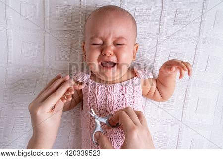 Crying Newborn Baby Cries While Cutting Nails, Horizontal Photo