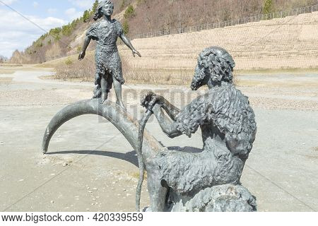 Statue Of Primitive Man And Girl. Khanty-mansiysk City, Russia - May 3, 2021