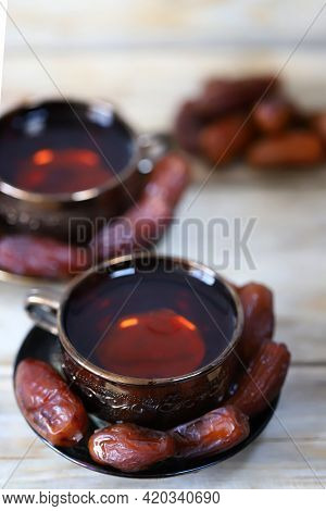 Date Tea. Dates In A Bowl On A Wooden Surface. The Benefits Of Dates. Ramadan Concept.