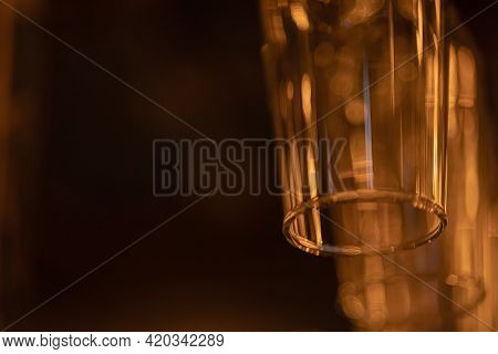 Glass Goblets For Wine, Champagne, Alcoholic Drinks Hang Upside Down Above The Bar. Warm Orange Even
