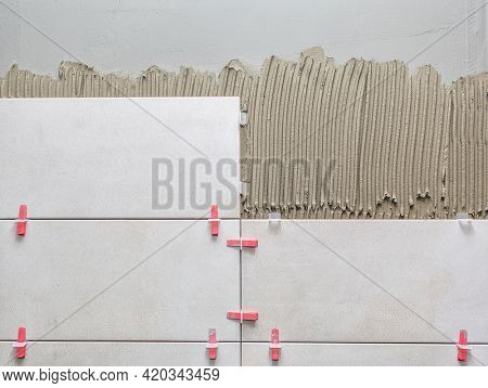 Ceramic wall tile in position over adhesive with lash tile leveling system